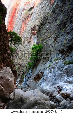 SAKLIKENT CANYON, TURKEY - OCTOBER 06, 2011: Tourists between the giant rocks and mountain walls - stock photo