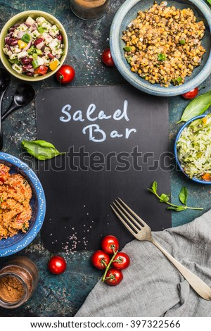 Salad bar with various healthy vegetarian salads dish, fork and black chalkboard, top view, frame. Inscription salad bar on blank chalkboard.  Healthy food and vegetarian Eating concept - stock photo