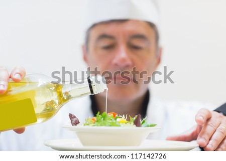 Salad being dressed by chef in kitchen - stock photo