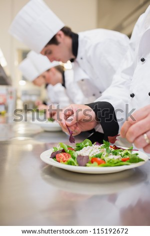 Salad being garnished by chef in the kitchen - stock photo
