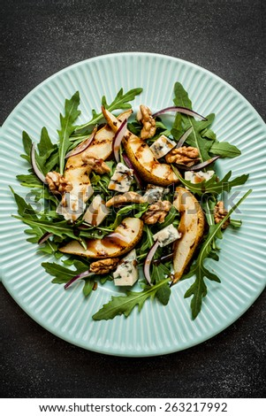 Salad - blue cheese, pear, arugula, walnuts, red onion and balsamic vinegar dressing on pastel blue plate from above. Black chalkboard as background. - stock photo