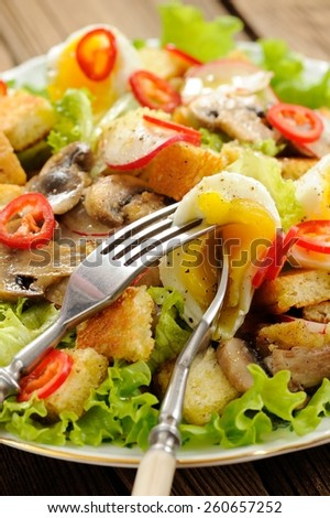 Salad Caesar with mushrooms, eggs, chili and radish with two forks closeup