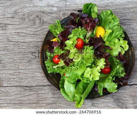 Salad. Colorful salad. Salad in dark brown ceramic plate on wood table  with free text space. Vegetarian salad dish on wooden background  . - stock photo