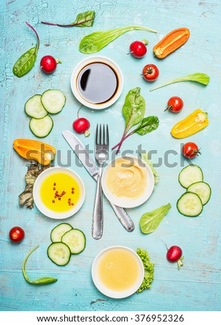 Salad dressing ingredients: vinegar ,mustard,oil and honey with vegetables. Cutlery with salad ingredients, top view. Flat lay of healthy  lifestyle or detox diet food  concept, - stock photo