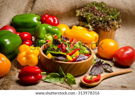 salad from bell pepper and basil in a wooden bowl on wooden table - stock photo