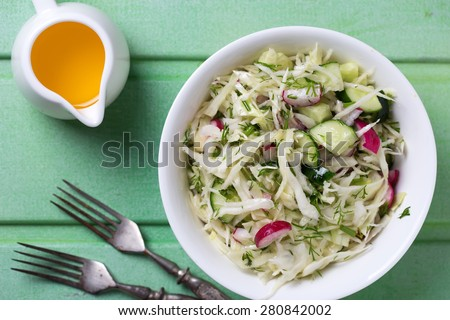 Salad from cabbage, herbs, cucumber, onion and radish in bowl on green wooden background. Coleslaw. Selective focus. - stock photo