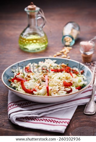 Salad from cabbage with red pepper and pine nuts.selective focus - stock photo