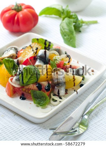 Salad from fresh organic yellow and red tomatoes with ancovy and onion