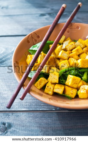 Salad from fried tofu with curry and fresh spinach in brown bowl with chopsticks. Close up - stock photo