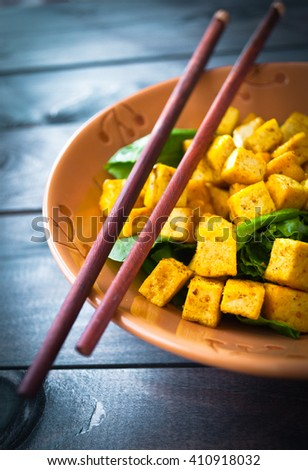 Salad from fried tofu with curry and fresh spinach in brown bowl with chopsticks. Vegetarian meal - stock photo