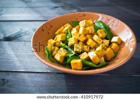 Salad from fried tofu with curry and green leaves of fresh spinach in ceramic bowl. Space for text - stock photo