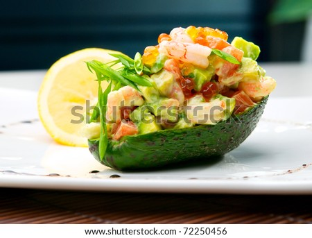 Salad from prawn and avocado on the table in cafe. Defocused background - stock photo