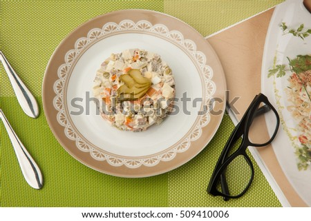 salad in a plate with book and glasses and cutlery on a green tablecloth