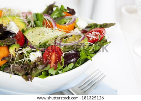 Salad in white bowl.  Mixed greens with black olives, tomatoes, and lots of vegetables. - stock photo