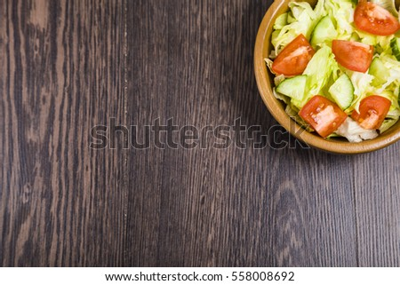 Salad in wooden bowl on a dark table close-up. Concept of healthy nutrition and diet.
