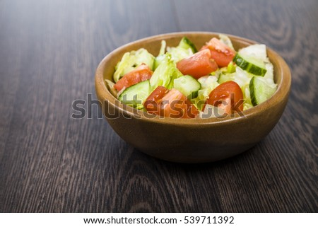 Salad in wooden bowl on a table close-up. Concept of healthy nutrition and diet.
