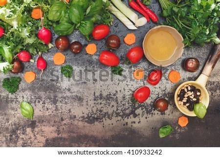 Salad ingredients and seasonings on dark background. Top view, vintage toned image, blank space - stock photo