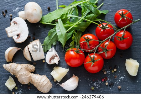 Salad ingredients - cherry tomatoes, mushrooms, ginger, garlic, ruccola, pepper, cheese on dark stone background, top view - stock photo