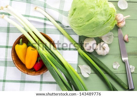 Salad ingredients on wooden table - stock photo