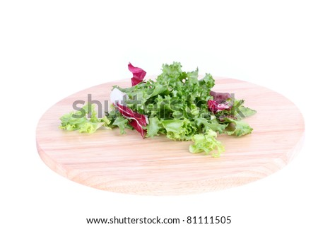 Salad leafs on wooden board isolated on white