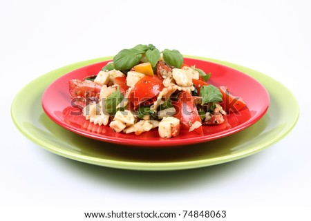 Salad - made of farfalle pasta, tomato, salami, bell pepper and mozzarella, decorated with basil - stock photo
