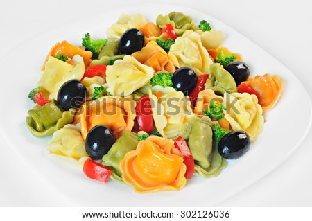 Salad made with tortellini, olives, broccoli, red pepper, on a plate, white background