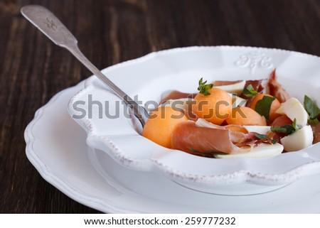 Salad melon with ham, eggs, mozzarella and Basil.selective focus - stock photo