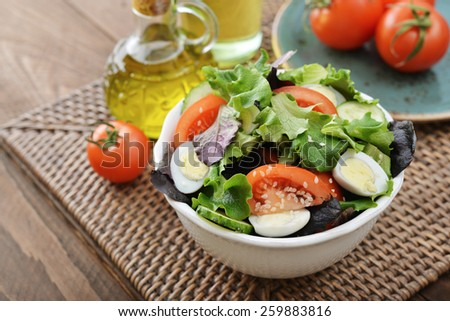 Salad mix with lettuce, tomato, cucumber and quail eggs in bowl on wooden background