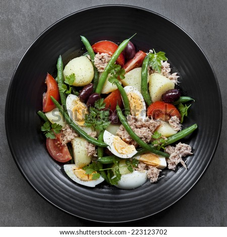 Salad nicoise.  Tuna with baby potatoes, eggs, beans, tomatoes, olives and parsley. - stock photo