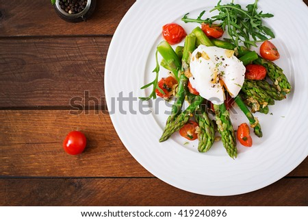 Salad of asparagus, tomatoes and poached egg. Top view - stock photo