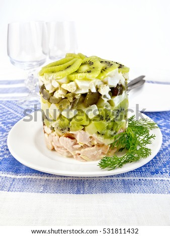 Salad of chicken, boiled potatoes, eggs, pickled cucumber and kiwi in a plate on a background of a linen tablecloth