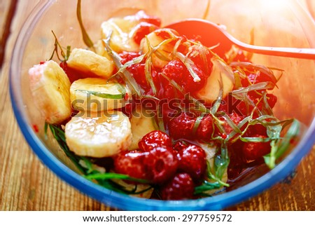salad of fresh bananas, raspberries, estragon and honey in transparent plate on wooden background. Selective focus - stock photo