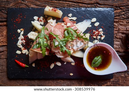 salad of fresh melon with thin slices of prosciutto, arugula leaves and balsamic sauce top view - stock photo