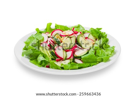 salad of fresh vegetables on a white plate with nuts