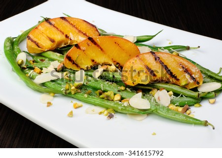 Salad of green beans , peaches, almonds, pistachios and sprinkled with Parmesan - stock photo