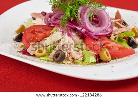 Salad of lettuce, tomato, chicken meat, olive, greens, onion