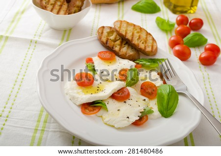 Salad of mozzarella and tomatoes with basil and olive oil