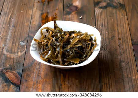 salad of pickled kelp in a plate on the wooden table - stock photo