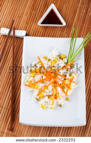 Salad of rice with sauce and sticks on bamboo mat - stock photo