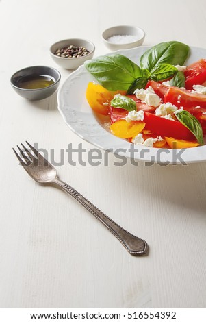 Salad of ripe tomatoes with basil and feta cheese on white teralke. Vegetarian food. Healthy breakfast. Light wood background