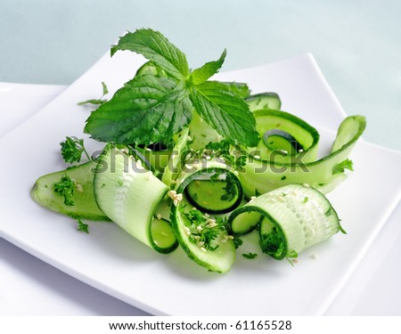 Salad of sliced green cucumbers with herbs and sesame seeds with mint leaves - stock photo