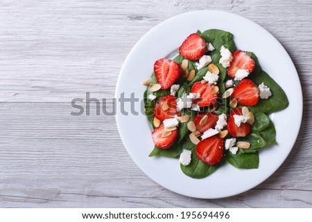 Salad of spinach, strawberries, cheese and almonds on the table top view  - stock photo