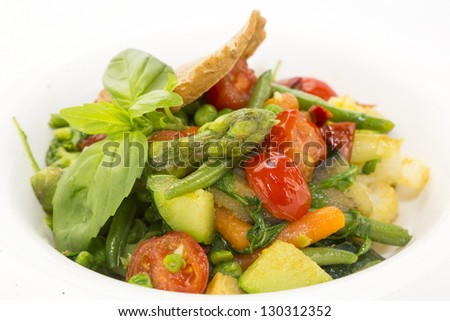 salad of steamed vegetables on a white plate in a restaurant - stock photo