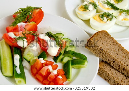Salad of tomatoes and cucumbers, eggs and bread on a light plane. - stock photo