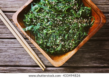 Salad of wakame in wooden bowl with chopsticks - stock photo