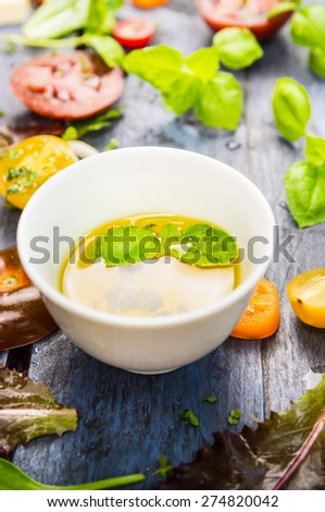 Salad oil dressing with tomatoes and basil on blue rustic background, close up - stock photo
