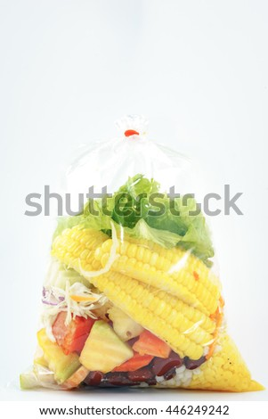 Salad packed in plastic bag on white background