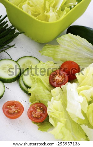 Salad preparation with cucumbers, lettuce, cherry tomatoes and chives on modern white wood table setting, closeup vertical. - stock photo