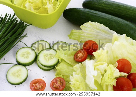 Salad preparation with cucumbers, lettuce, cherry tomatoes and chives on modern white wood table setting, closeup. - stock photo