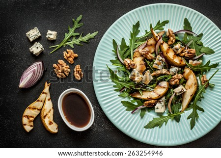 Salad recipe - blue cheese, pear, arugula, walnuts, red onion and balsamic vinegar dressing on pastel blue plate from above. Black chalkboard as background. - stock photo